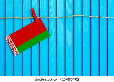 Flag of Belarus hanging on clothesline attached with wooden clothespins on aqua blue wooden background. National day concept.