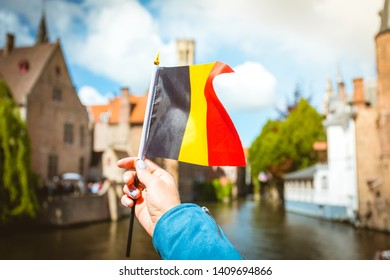 Flag of Belgium in female hand on background of panoramic city view with Belfort tower and famous canal in Brugge, Belgium.