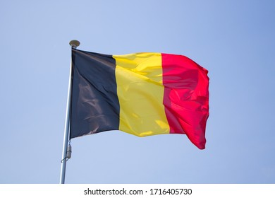 The flag of belgium waving on the wind behind a blue background