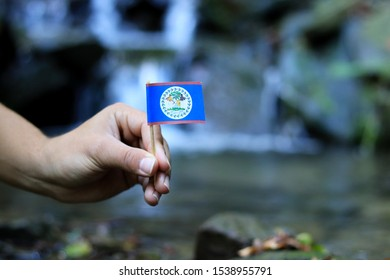 Flag of Belize on wooden stick. Afro american holds national athem near waterfall on stream in autumn times. Concept of humanity and nature. Belize in hand. Flag for packet. Symbol of citizens.