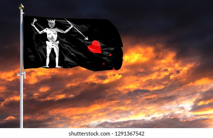 flag of Blackbeard Pirate on flagpole fluttering in the wind against a colorful sunset sky