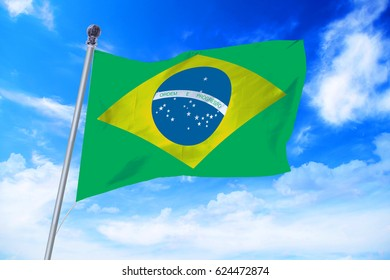 Flag of Brazil developing against a clear blue sky
