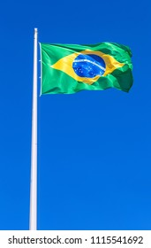 Flag of Brazil flying in the wind against the blue sky