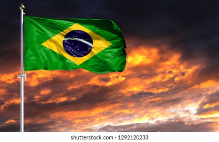 flag of Brazil on flagpole fluttering in the wind against a colorful sunset sky