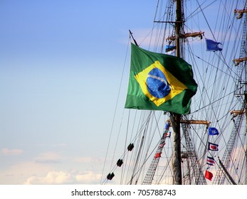 Flag of Brazil on a sailboat in the background of a blue sky. Thematic sea days in Tallinn, Estonia. Copy space.
