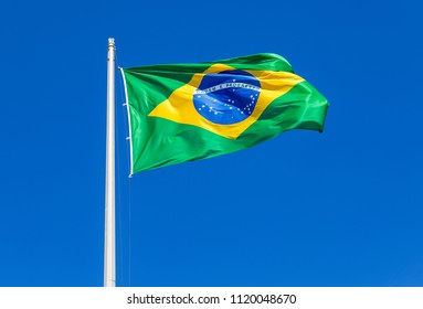 Flag of Brazil waving in the wind against the blue sky