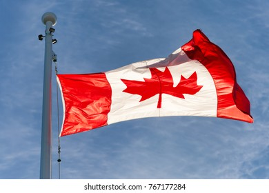 Flag of Canada flying against a blue sky in Vancouver, BC, Canada