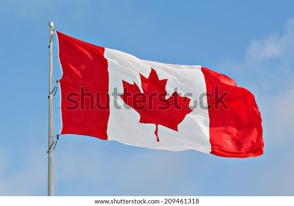 Flag of Canada flying against a blue sky.