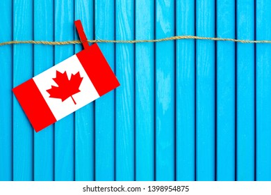 Flag of Canada hanging on clothesline attached with wooden clothespins on aqua blue wooden background. National day concept.