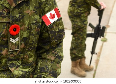 Flag of Canada on the military uniform and soldier with weapon on the background. Canadian soldiers. Canadian Army. Remembrance Day.Poppy day.