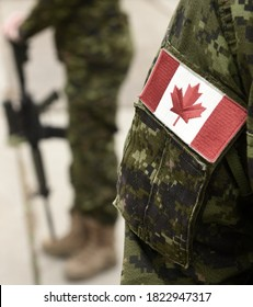 Flag of Canada on the military uniform and soldier with weapon on the background. Canadian soldiers. Canadian Army. Remembrance Day. Canada Day.