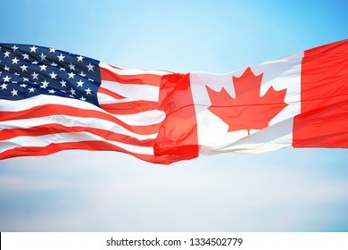 Flag of Canada and the USA against the background of the blue sky