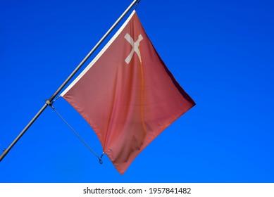 Flag of canton Schwyz blowing in the wind. Photo taken April 14th, 2021, Schwyz, Switzerland.