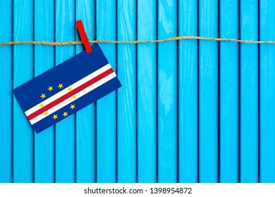 Flag of Cape Verde hanging on clothesline attached with wooden clothespins on aqua blue wooden background. National day concept.