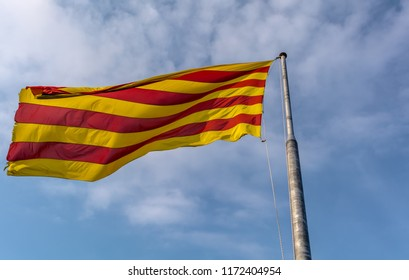 Flag of Catalonia waving in the breeze against blue sky. The flag is called The Senyera (flag in Catalan) and consists of four red stripes on yellow field. It represents the Catalan Nation and culture