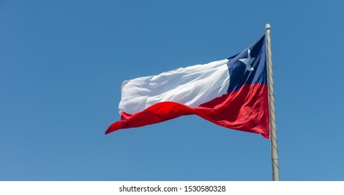 Flag of Chile flies in a strong wind against a bright blue sky with sun glare. Patriotic symbol of Chile, South America.