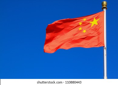 Flag of China against blue sky.