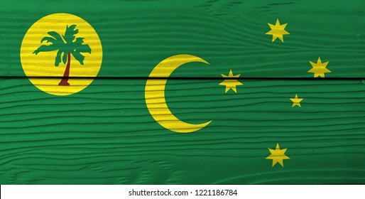 Flag of Cocos (Keeling) Islands on wooden wall background. Grunge Cocos flag texture, a palm tree on a gold disc, crescent and southern cross on green.