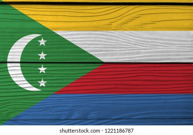 Flag of Comoros on wooden wall background. Grunge Comoros flag texture, yellow white red and blue with  green chevron, crescent and star.