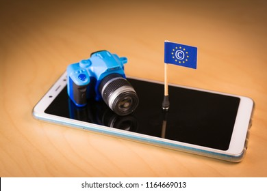 Flag with Copyright symbol and small camera over a smartphone. Symbolizing the EU Directive on Copyright in the Digital Single Market or CDSM. Art. 13 is known as meme ban