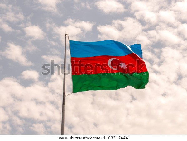 flag of the country Azerbaijan developing in the wind against the blue sky