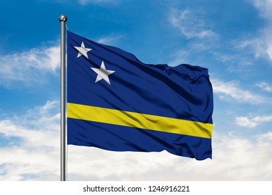 Flag of Curacao waving in the wind against white cloudy blue sky.