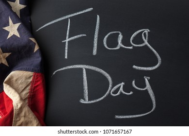 Flag Day sign handwritten on a chalkboard bordered by a vintage American flag