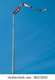 Flag of Denmark up high with clear blue sky background vertical image
