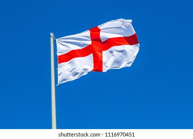 Flag of England waving in the wind against the blue sky