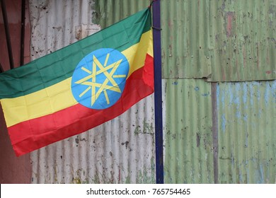 The flag of Ethiopia in front of a green and grey corrugated metal wall, on flag pole flying in Addis Ababa, Ethiopia