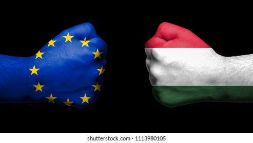 Flag of European Union and Hungary painted on two clenched fists facing each other on black background/Hungary in the EU concept