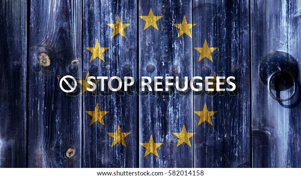 Flag of the European Union painted on an old wooden door. Next to the door handle text Stop Refugees.