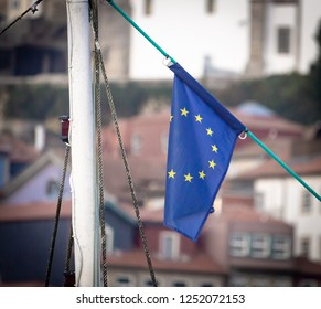 A flag of the European Union waves against an old town background.