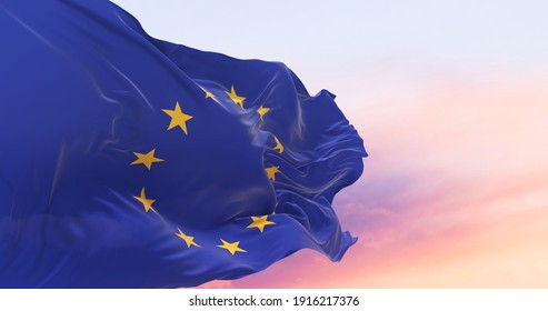 Flag of the European Union waving in the wind on flagpole against the sky with clouds on sunny day