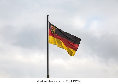 Flag of the Federal Republic of Germany against the cloudy sky background.