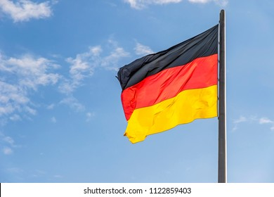 Flag of Federal Republic of Germany waving on the wind on the top of German parliament building (Bundestag) in Berlin, Germany. Blue sky background