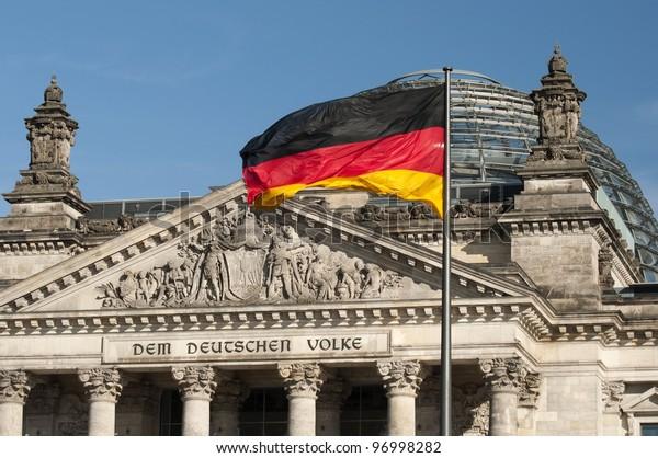 flag of the Federal Republic of Germany is waving in front of the national german parliament, Flagge der Bundesrepublik Deutschland weht vor dem Reichstag, Sitz des deutschen Bundestages, Berlin