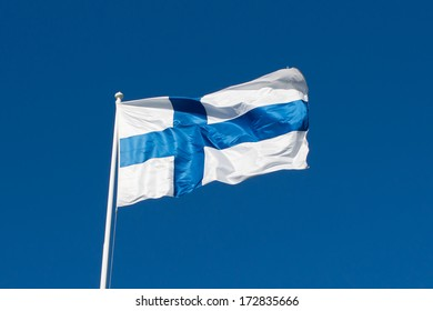 Flag of Finland before blue sky. Flag in the wind. Windy, sunny weather. Finland, finnish flag. Cross flag.