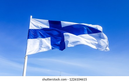 The flag of Finland fluttering in the wind on the blue sky background.