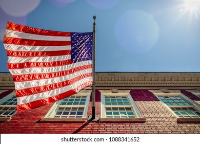 A flag flying over a brick building, with a few sun spots, in Alexandria, Virginia.