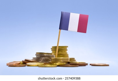 Flag of French Guiana in a mixed stack of european coins and a blue background.(series)