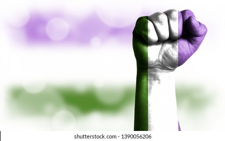 Flag of genderqueer pride painted on male fist, strength,power,concept of conflict. On a blurred background with a good place for your text.