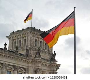 The flag of Germany flutters against the background of the Reichstag building. Berlin