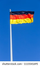 Flag of Germany flying in the wind against the blue sky