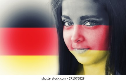 The flag of Germany on the face of a smiling woman. / Color effects and custom white balance is added to this photo.