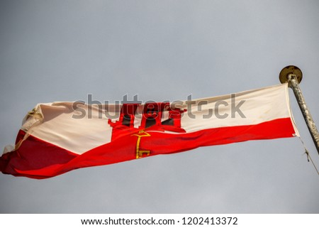 The flag of Gibraltar. Gibraltar is a British Overseas Territory located on the southern tip of Spain.