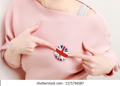 The flag of Great Britain, commonly known as the Union Jack printed on button badge, holding by woman in her beautiful hand.