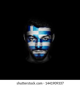 Flag of Greece painted on a face of a man on black background.