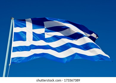 Flag of Greece waving in the wind, under a clear blue sky, shot from low angle