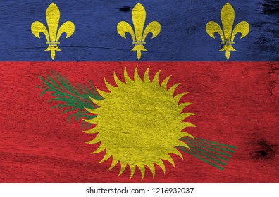 Flag of Guadeloupe Local on wooden plate background. Grunge Guadeloupe Local flag texture. red field with yellow sun and green sugar cane, and a blue stripe with yellow fleurs-de-lis on the top.